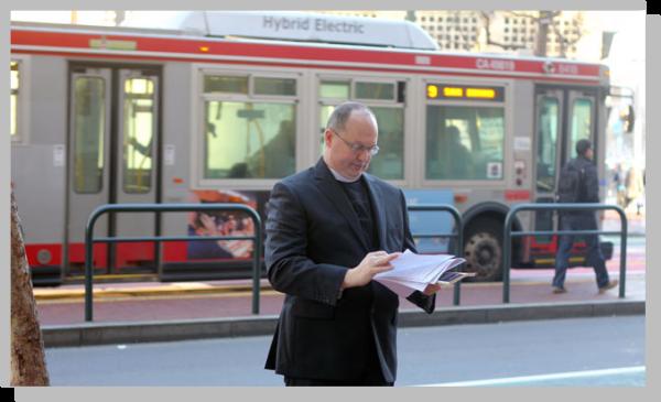 startup priest reading api docs outside twitter in san francisco